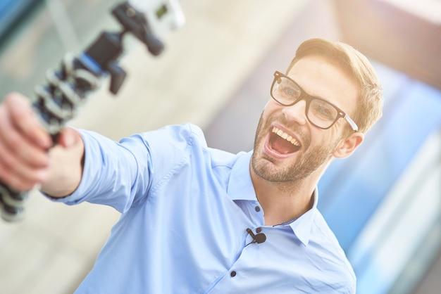 파란색 셔츠를 입고 짐벌을 들고 안경을 쓴 젊은 행복한 남성 블로거