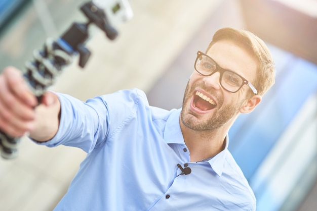 Creating new content young happy male blogger wearing blue shirt and eyeglasses holding a gimbal