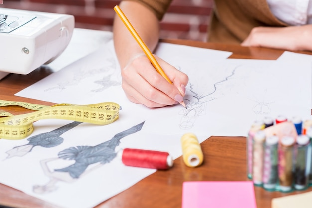 Creating new fashion look. close-up of woman drawing fashion sketch while sitting at her working place