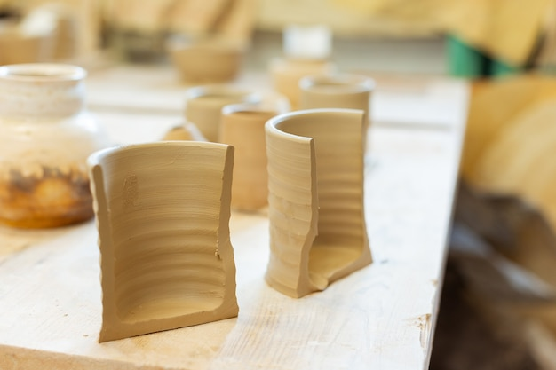 Creating new figures. fresh unprocessed clay pot being separated on two pieces and waiting for oven baking