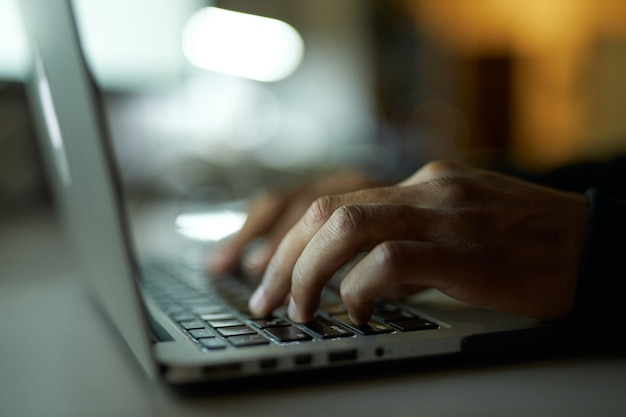作成プロセスは、テーブルに座ってラップトップで作業を入力している若い男の手のショットをクローズアップします。