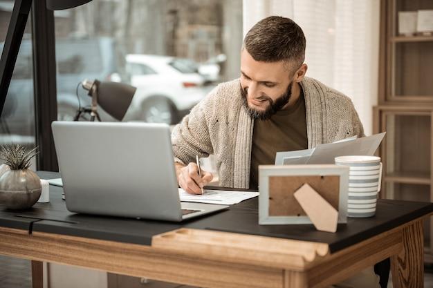 スケジュールの作成。彼のカレンダーで会議を書き留める灰色のカーディガンで笑顔のポジティブなビジネスマン