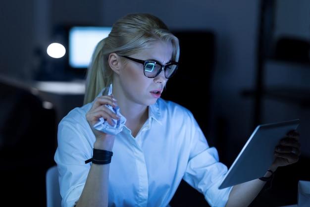 새 프로젝트 만들기. 사무실에 앉아 프로젝트를 진행하는 동안 태블릿을 사용하는 세심한 참여 아름다운 it 여성