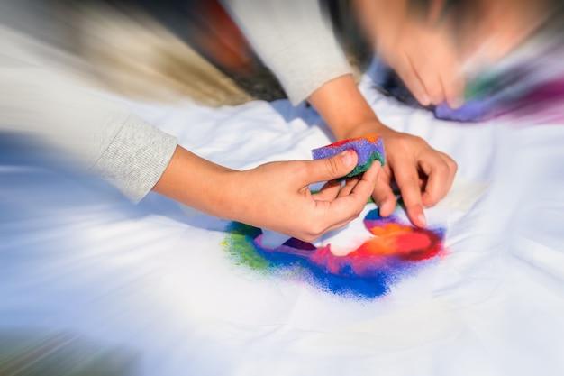 Создание собственной мастерской по изготовлению футболок на улице. рука, наносящая краску на рубашку