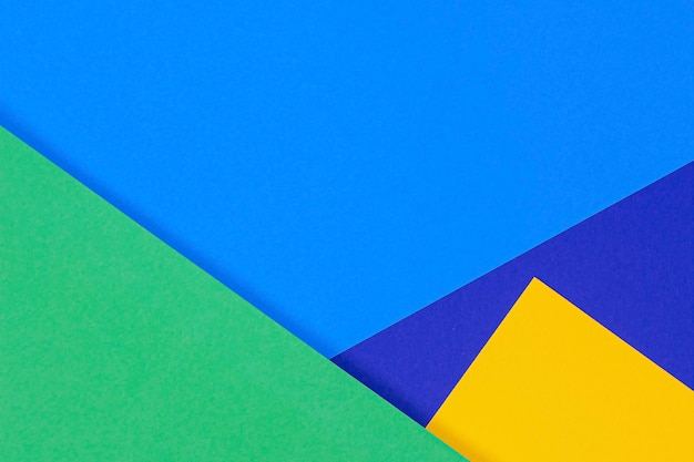 Creative abstract blue, green and yellow color geometric paper compositon wall, top view