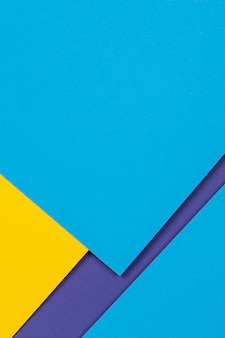 Creative abstract blue and yellow color geometric paper compositon wall, top view