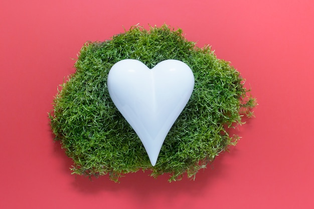 Creative abstract composition with white porcelain heart on green forest moss on pink surface