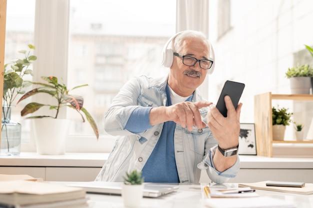 オフィスの職場のそばに座ってプレイリストを探しているカジュアルウェアとヘッドフォンで創造的な老人