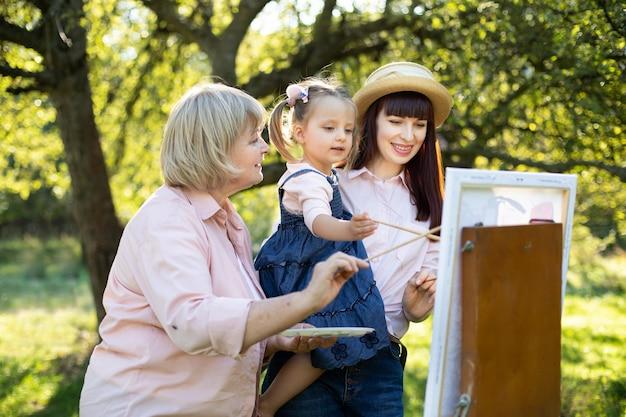 クリエイティブでアートの子供たちの開発コンセプト。春の公園で、3 世代の女性、引退した祖母、若いきれいな母親、イーゼルに絵を描くかわいい小さな女の子。