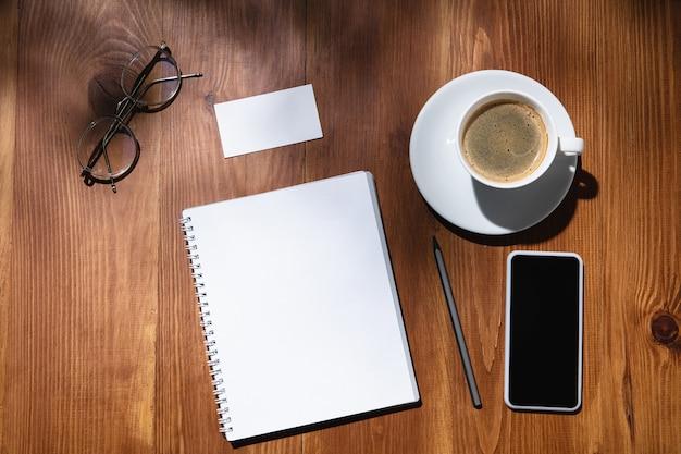 ホームオフィスの創造的で居心地の良い職場、テーブルの表面に植物の影が付いたインスピレーションあふれるモックアップ