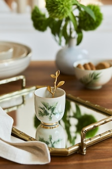 Креативная и элегантная композиция столовой с шикарным фарфором, золотым подносом и красивыми личными аксессуарами. роскошные апартаменты. красота в деталях. шаблон.