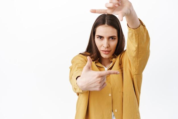 완벽한 각도를 찾고 있는 창의적이고 열정적인 여성, 손 프레임 카메라 제스처 및 결정된 수심에 찬 표정을 통해 찾고, 무언가를 만들고, 흰 벽 위에 서 있습니다.