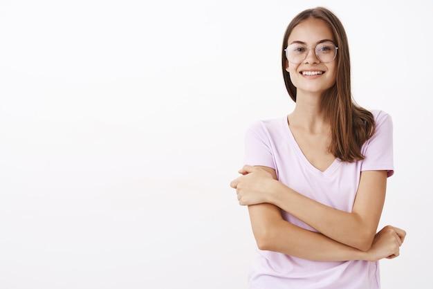 Креативная и умная красивая женщина в круглых очках и блузке, держащая руку за руку в застенчивой небезопасной позе, улыбается, чувствуя себя неуверенно в первый день на работе над белой стеной