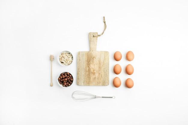 Творческий аранжированный набор сырых ингредиентов здоровой пищи на белом фоне. плоская планировка, вид сверху