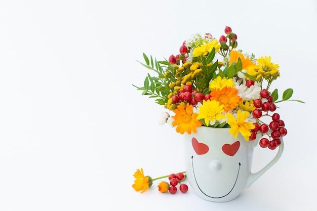 果実と白い背景に笑顔でコーヒーカップの創造的な配置秋の花束。秋のシーズンのコンセプト、9月、10月、11月、愛。白い背景で隔離。
