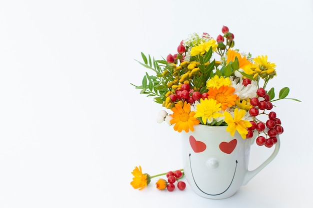 Creative arrangement autumn bouquet with berries and coffee cup with a smile on a white background. autumn season concept, september, october, november, love. isolated on a white background.
