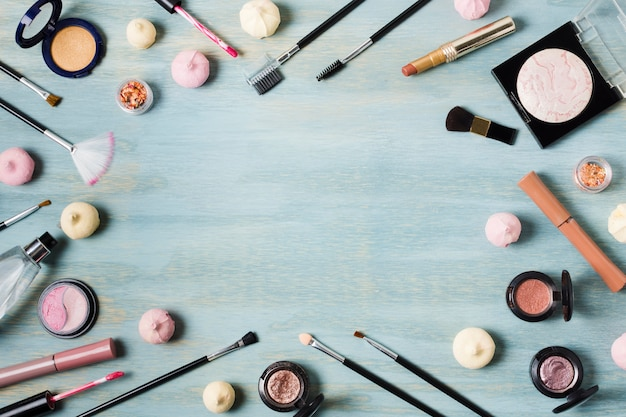 Creative arrangement of cosmetics on colored surface