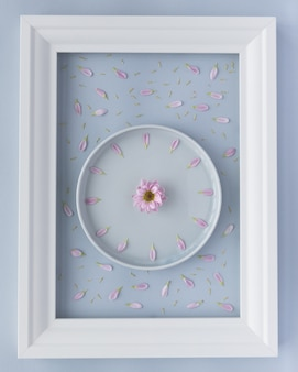 Creative arrangement of lavender plate with chrysanthemum flower clock created from fresh violet petals