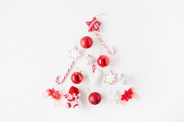 크리스마스 공, 과자, 흰색 바탕에 장난감으로 만든 밝은 빨간색 크리스마스 트리의 창조적 인 배열.