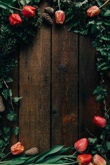 튤립과 어두운 나무 벽에 나뭇잎의 창조적 인 배열. 평평하다.