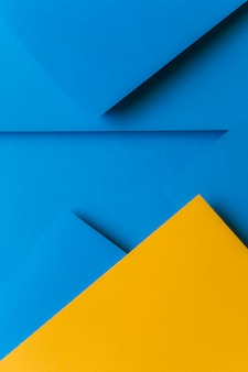 Creative arrangement of yellow and blue colored paper creating an abstract background