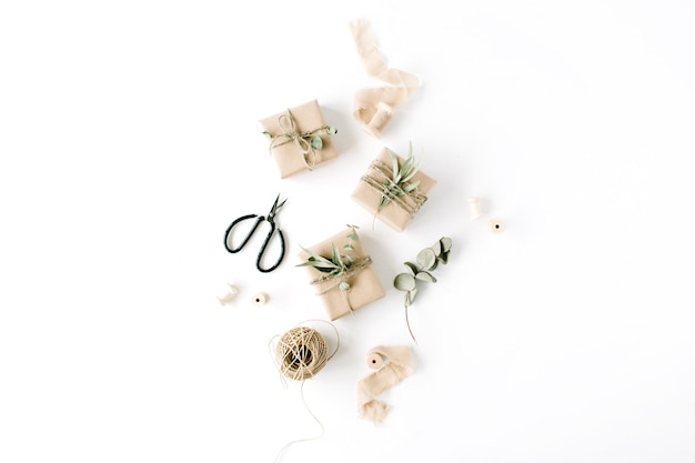 Творческий образец расположения ремесленных коробок и зеленых ветвей на белом фоне.