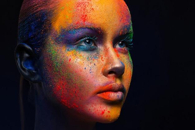 創造的な芸術は構成します。ホーリー色。彼女の顔にペンキの明るくカラフルなミックスと若者のファッションモデルの肖像画。