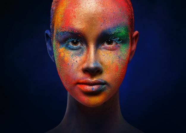創造的な芸術は構成します。彼女の顔にペンキの明るくカラフルなミックスと若者のファッションモデルの肖像画。カラーファンタジー、芸術的な化粧。