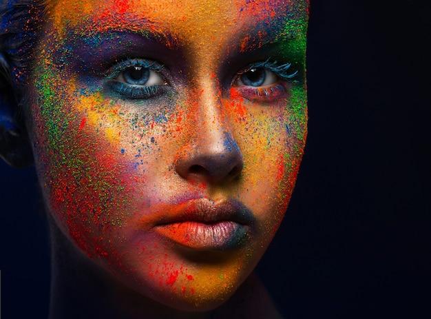 創造的な芸術は構成します。目を閉じて、彼女の顔にペンキの明るいカラフルなミックスで若者のファッションモデルの肖像画。カラーファンタジー、芸術的な化粧。
