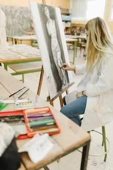 黒いクレヨンでイーゼルにスケッチをするスツールに座ってクリエイティブアーティスト