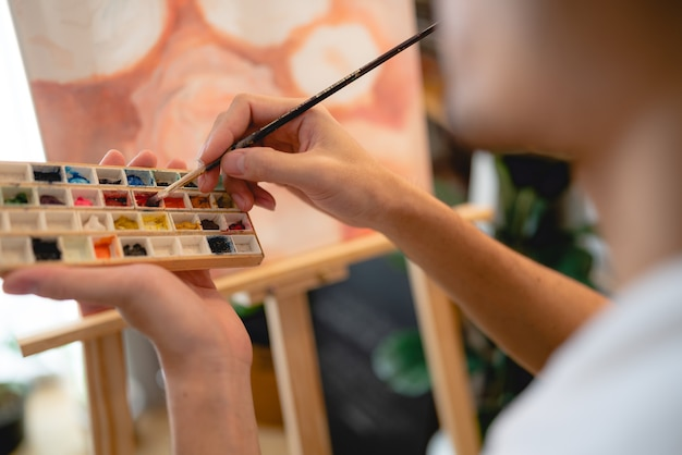Креативный художник, работающий над цветным искусством для рисования картины кистью в хобби, мастерская по изготовлению инструментов для акварельной кисти с холстом в студии, мольберт с палитрой и дизайн фона