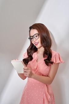 Творческая азиатская работница, находящаяся в помещении, пишет заметки и планирует свой график, смотрит в камеру. портрет молодой довольно внештатной женщины работает удаленно, стоя на фоне студии белой стене.