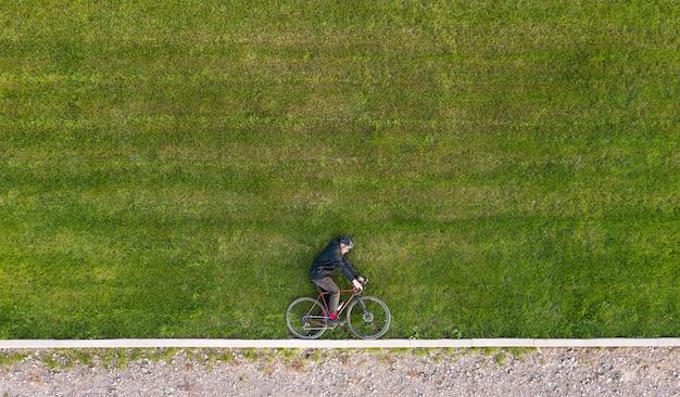 自転車で緑の芝生に横たわっているサイクリストの創造的な秋の構成。最小限のコンセプト。