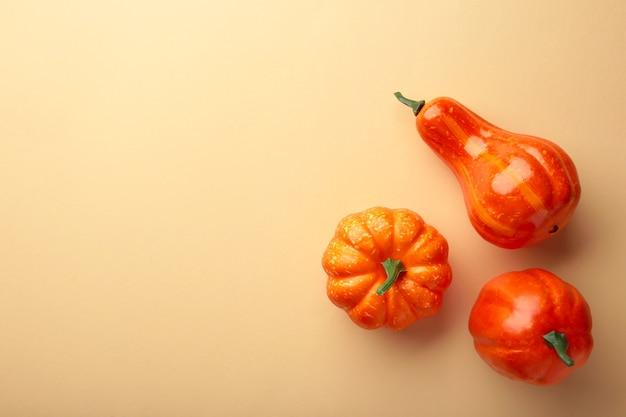 創造的な秋の構成。ベージュの背景にオレンジ色のカボチャ。