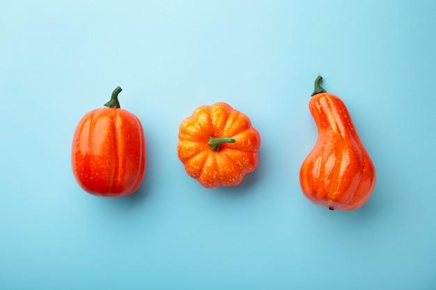 創造的な秋の構成。青い背景にオレンジ色のカボチャ。