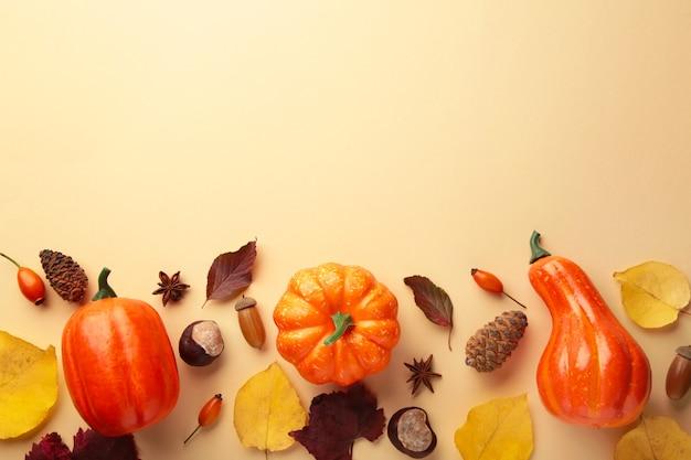 創造的な秋の構成。ベージュの背景に葉を持つオレンジ色のカボチャ。上面図