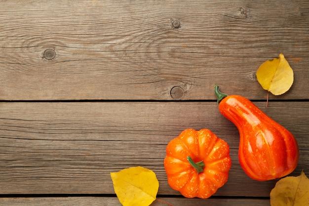創造的な秋の構成。灰色の木製の背景の葉とオレンジ色のカボチャ。上面図