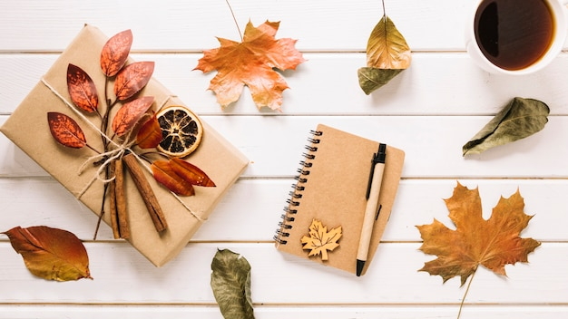 Creative autumn composition with gift, notebook and tea