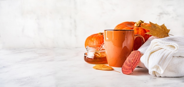 Creative autumn composition with orange cup, pumpkin and jar of honey