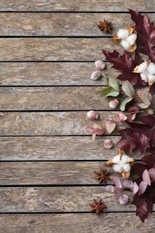 Творческая осенняя осенняя композиция на день благодарения с декоративными сушеными листьями. плоская планировка, вид сверху, копия пространства, натюрморт деревянный фон для поздравительной открытки. цветочная, ботаническая концепция.