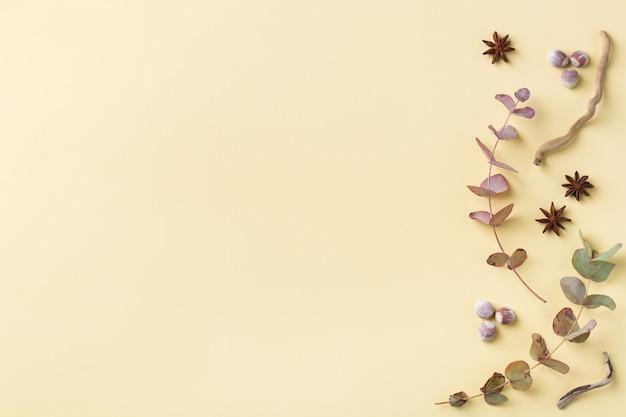 장식용 말린 잎이 있는 창의적인 가을 추수 감사절 구성. 평평한 평지, 위쪽 보기, 복사 공간, 인사말 카드의 정물 노란색 배경. 꽃, 식물 개념입니다.