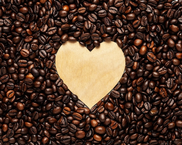 Creative backdrop made of wooden heart with coffee beans.