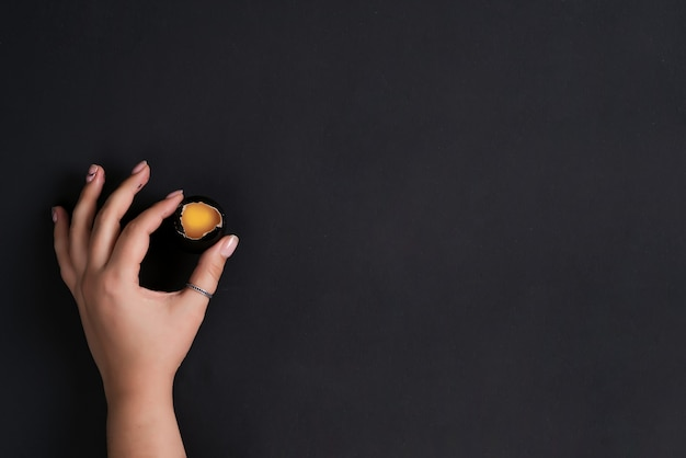 女性の手で創造的な背景は、同じ色の背景に黄色の卵黄で壊れたイースター塗装黒卵を保持します。