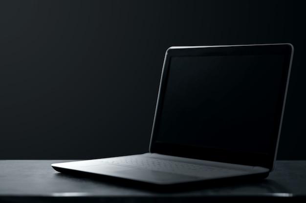 創造的な背景暗いラップトップは暗い背景の上に立っています。現代の技術コンセプト。