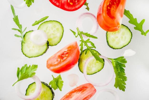創造的な背景、レイアウト、サラダの新鮮な健康的な食事のコンセプト、新鮮な生野菜トマトパセリ玉ねぎきゅうり緑、シンプルなパターン