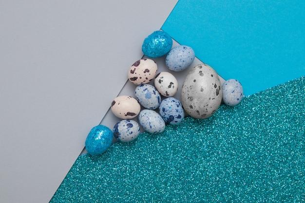 Креативный фон из комбинации бумаги, глиттера и яиц в сине-зеленых оттенках