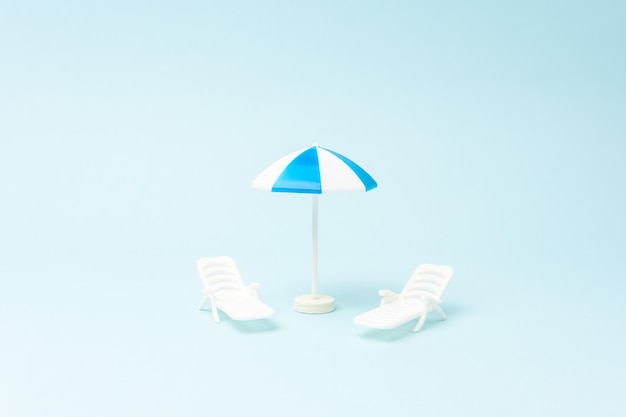 Creative background with sunbeds and sun umbrella on pastel blue background