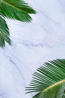大理石のテーブルに熱帯のヤシの葉と創造的な背景。最小限の自然、花、休暇夏休みのコンセプト。コピースペース、フラットレイ、上面図