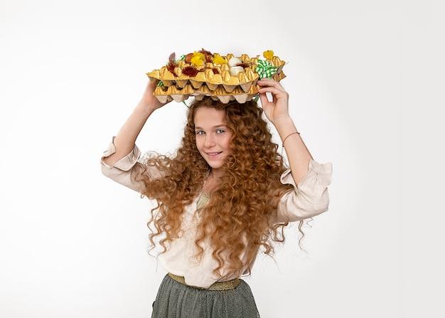 Креативная красивая девочка-подросток с кудрявыми рыжими волосами положила на голову картонную коробку с пасхальными украшениями в виде яиц и весело смеялась