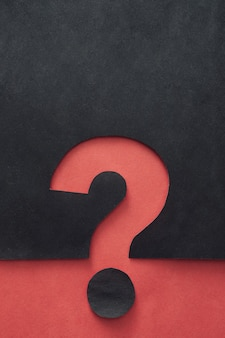 Creative bicolor background with red and black question mark cutout and copy space above for conceptual themes
